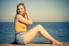 Lovely blonde girl relaxing outdoor by seaside Stock Images