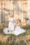 Lovely blonde girl sisters in white dresses and straw hats laugh and eat apples in the countryside Stock Image