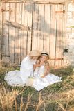 Lovely blonde girl sisters in white dresses and straw hats laugh and eat apples in the countryside Stock Photo
