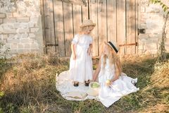 Lovely blonde girl sisters in white dresses and straw hats laugh and eat apples in the countryside Stock Photography