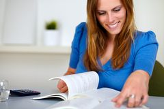 Lovely blonde girl smiling and reading Stock Images