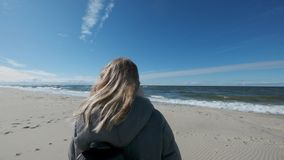 Lovely blonde girl steps on a sandy beach on a background of blue sea waves, blue sky. Slow motion stock footage