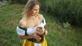 Lovely blonde waitress at the music festival Oktoberfest in Germany. A girl in a Bavarian suit walks the grass and. Carries beer to customers stock video
