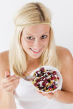 Lovely blonde woman eating muesli. Portrait of lovely blonde woman eating muesli with fruit at breakfast Royalty Free Stock Image