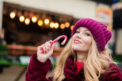 Lovely young woman posing with Christmas candy cane at the stree Stock Images