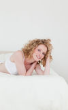 Lovely blonde woman relaxing. While lying on her bed in her appartmant Stock Photos