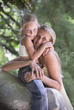 Lovely blonde young girl and mother hug outdoor. Young mother and her little daughter hug Stock Image