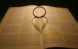 Lovely book. Lens-shadow builds heart on a book Royalty Free Stock Image