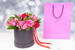Lovely bouquet of pink and red roses and red ribbon in a circula. R black box near pink gift bag. Valentines and anniversary concept Stock Photo