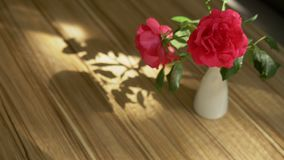 A lovely bouquet of roses and freesia and the shadow of it on the table, lit by sunlight through the curtain royalty free stock image