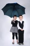 Lovely boy and girl standing under umbrella Stock Photos