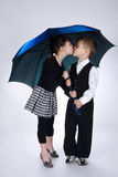 Lovely boy and girl standing under umbrella Royalty Free Stock Images