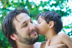 Lovely boy and his father. Holding him in hands in nature stock photo