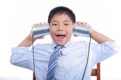 Lovely boy listen tin can telephone. In studio Stock Photo