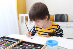 Lovely boy paints Stock Photos