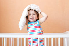Lovely boy with pillow on the head  in white bed Royalty Free Stock Photo