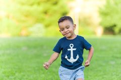 Lovely boy playing and running in a park outdoors stock photography