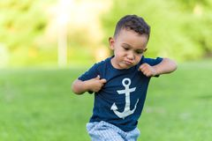 Lovely boy playing and running in a park outdoors stock photo