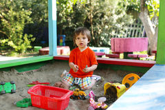 Lovely boy playing with sand on playground in summer Stock Photography