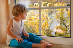 Lovely boy of two years looking out of the window on yellow autu Royalty Free Stock Photography