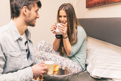 Lovely boyfriend bring some breakfast to his girlfriend in the m Royalty Free Stock Images