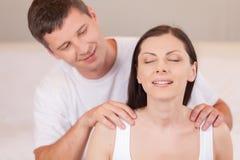 Lovely boyfriend massaging girlfriend's shoulders. Stock Images