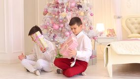 Lovely boys brothers study gifts and sit on floor in bedroom with Christmas tree. Charming children of men`s twins are shaking gifts in their hands, they stock video footage