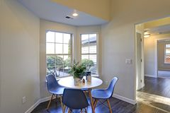 Lovely breakfast nook with white round table and blue chairs. Lovely breakfast nook fitted with white round table and blue chairs stock photo