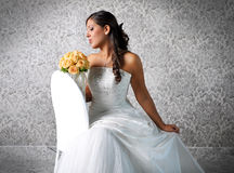A lovely bride. Looks down at her bouquet stock photography