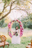 The lovely bride with the bouquet is sitting in the wedding flower arch hanging on the tree at the background of the. Sunny field Stock Images