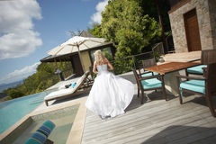 Lovely bride coming across pool area before wedding. Royalty Free Stock Photo