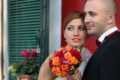 Lovely bride and groom in the city sunny day flower bouquet Stock Images