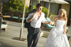 Lovely bride and groom coming across pool area after wedding. Royalty Free Stock Image