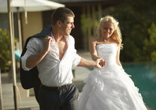 Lovely bride and groom coming across pool area after wedding. Stock Images