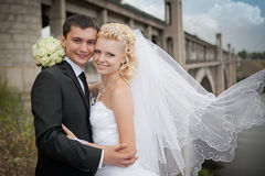 Lovely bride and groom near a bridge Stock Photo