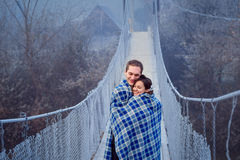 Lovely bride and groom wripped in blanket softly hugs on the wooden bridge. Honeymoon at mountains Royalty Free Stock Image