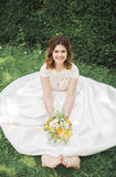 Lovely bride sitting on ground holding a bouquet smiling at camera Royalty Free Stock Photo