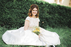 Lovely bride sitting on ground holding a bouquet smiling at camera Royalty Free Stock Images