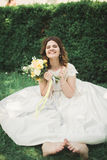 Lovely bride sitting on ground holding a bouquet smiling at camera Royalty Free Stock Photography