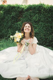 Lovely bride sitting on ground holding a bouquet smiling at camera Stock Image