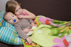 Lovely brother and sister lying in bed at home. Stock Photo