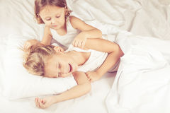Lovely brother and sister lying in bed at home. Concept of Brother And Sister Together Forever Royalty Free Stock Images