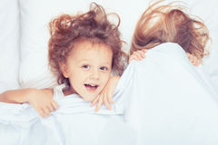Lovely brother and sister lying in bed at home. Concept of Brother And Sister Together Forever Stock Photo