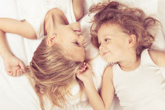 Lovely brother and sister lying in bed at home. Stock Photography