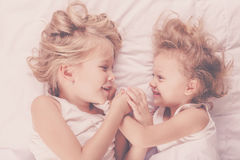Lovely brother and sister lying in bed at home. Royalty Free Stock Images