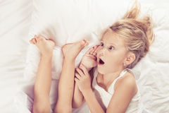 Lovely brother and sister lying in bed at home. Royalty Free Stock Photography