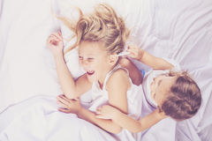 Lovely brother and sister lying in bed at home. Royalty Free Stock Photos