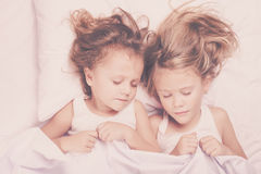 Lovely brother and sister lying in bed at home. Stock Images