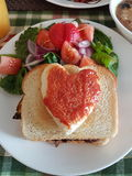 Lovely brunch. With heart bread and salad Stock Image