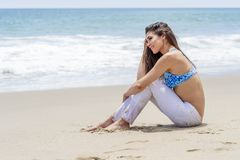 Lovely Brunette Bikini Model Relaxing On The Shoreline At The Beach. A gorgeous brunette bikini model lounging on the shoreline at the beach on a sunny day royalty free stock photo